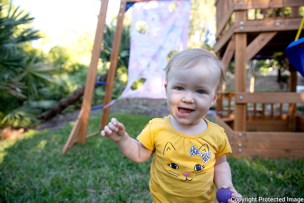 A baby plays in the backyard