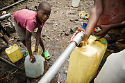 Children fill jericans of water from a pipe in the Mugunga II IDP camp on the outskirts of Goma, Democratic Republic of Congo, on Wednesday December 17, 2008.