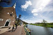 In Oud-Zuilen rijden fietsers langs een kerkje aan de Vecht.<br /> <br /> In Oud-Zuilen cyclists pass a church near the Vecht.