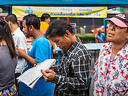 """07 AUGUST 2014 - BANGKOK, THAILAND:     A man reads a newspaper while he waits for a food distribution program to start at Pek Leng Keng Mangkorn Khiew Shrine in Bangkok. Thousands of people lined up for food distribution at the Pek Leng Keng Mangkorn Khiew Shrine in the Khlong Toei section of Bangkok Thursday. Khlong Toei is one of the poorest sections of Bangkok. The seventh month of the Chinese Lunar calendar is called """"Ghost Month"""" during which ghosts and spirits, including those of the deceased ancestors, come out from the lower realm. It is common for Chinese people to make merit during the month by burning """"hell money"""" and presenting food to the ghosts. At Chinese temples in Thailand, it is also customary to give food to the poorer people in the community.  PHOTO BY JACK KURTZ"""