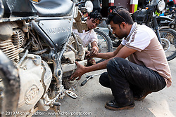 Muhammad Kurshid, Motorcycle Sherpa's Lead Mechanic (and master of roadside repairs) does his magic on our Ride to the Heavens motorcycle adventure in the Himalayas of Nepal. On the second day of riding, we went from Nuwakot to Pokhara. Tuesday, November 5, 2019. Photography ©2019 Michael Lichter.