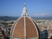 The dome from the Basilica di Santa Maria del Fiore, more commonly called the 'Duomo'. Florence, Italy. Started in 1296 based on Arnolfo di Cambio's design, but was not complete until 1436 when Filippo Brunelleschi engineered the dome. One of Italy's largest churches. The dome itself is octagonal, and uses a double shell design, made of sandstone and marble. Atop the dome sits a lantern with a copper ball and cross at it's peak.