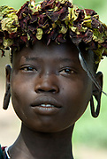Young Girl with flower head gear, Mursi Tribe, Mago National Park, Lower Omo Valley, Ethiopia, portrait, person, one, tribes, tribal, indigenous, peoples, Southern, ethnic, rural, local, traditional, culture, primitive,