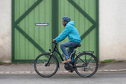 Senior man with cycling helmet on his bicycle, Bavaria, Germany