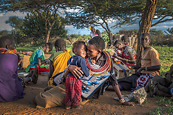 Ntipiyon Nonguta and her son Bernard, 1, relax with their neighbors as they make  beaded belts for Loisaba Community Trust in Ewaso village in Laikipia in Northern Kenya.   These women are in a community surrounding Loisaba Conservancy and are being supported and given access to international markets. Revenue from ecotourism is reinvested into neighboring communities like Ewaso.