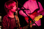 Schoolboys perform rock and roll song together as a band in a south London pub during a music showcase. The young boy sings into a microphone while playing his Fender guitar that has a sticker on the body asking to keep music live! In the background is a much older boy playing bass guitar. Organised by a south London guitar teacher who brings in sound equipment, the kids play their rehearsed songs for a private audience of parents and friends.