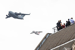 © Licensed to London News Pictures. 10/07/2018. London, UK. People watch from rooftops near Parliament Square as an RAF C-17 Globemaster and BAE146 fly over central London as part of the RAF100 flypast which celebrates the centenary of the Royal Air Force. Photo credit: Rob Pinney/LNP