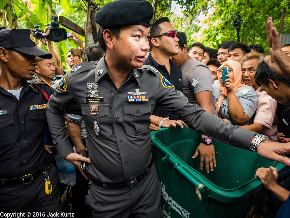 03 SEPTEMBER 2016 - BANGKOK, THAILAND: A Thai police officers forces his way into the Pom Mahakan community. Hundreds of people from the Pom Mahakan community and other communities in Bangkok barricaded themselves in the Pom Mahakan Fort to prevent Bangkok officials from tearing down the homes in the community Saturday. The city had issued eviction notices and said they would reclaim the land in the historic fort from the community. People prevented the city workers from getting into the fort. After negotiations with community leaders, Bangkok officials were allowed to tear down 12 homes that had either been abandoned or whose owners had agreed to move. The remaining 44 families who live in the fort have vowed to stay.      PHOTO BY JACK KURTZ