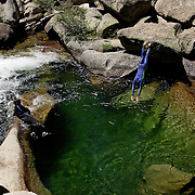 A woman jumps into a pool of water on the Tuolumne River in Yosemite National Park.