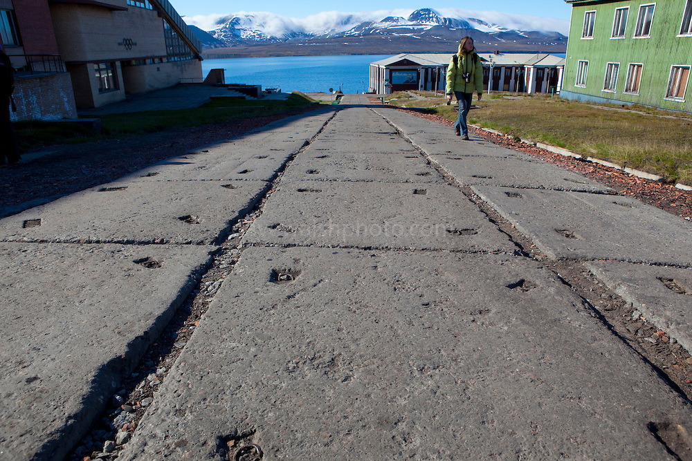 A tourist on the main street of Barentsburg, a Russian coal mining town in the Norwegian Archipelego of Svalbard. Once home to about 2000 miners and their families, less than 500 people now live here.