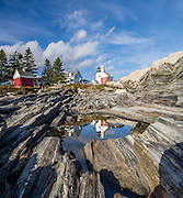A unique landscape of beautifully striped bedrock descends from Pemaquid Light to the Atlantic Ocean. Pemaquid Point Lighthouse was built in 1835 and commemorated on Maine's state quarter (released 2003). Visit Lighthouse Park at the tip of Pemaquid Neck in New Harbor, near Bristol, Lincoln County, Maine, USA. From Damariscotta on bustling US Highway 1, drive 15 miles south on Maine Route 130 to the park. The keeper's house (built 1857) is now the Fishermen's Museum at Pemaquid. Geologic history: Silurian Period sediments laid down 430 million years ago were metamorphosed underground into a gneiss 360-415 million years ago, and intruded by molten rock which cooled slowly, creating the park's exposed metamorphic gray rocks with dikes of harder, white igneous rock. Underground heat and pressure tortured and folded the rock layers into the striking patterns that are now pounded and polished by the sea and rough weather. The panorama was stitched from 4 overlapping photos.