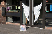 Angel wings on a shop door on 24th March 2021 in Birmingham, United Kingdom. A carrier bag placed outside asks the owner to reuse and repeat.