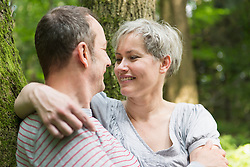 Mature couple looking at each other in forest, smiling