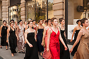 The women walk en mass down the sidewalk, past the men.