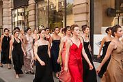 The women walk en mass down the sidewalk, past the men.