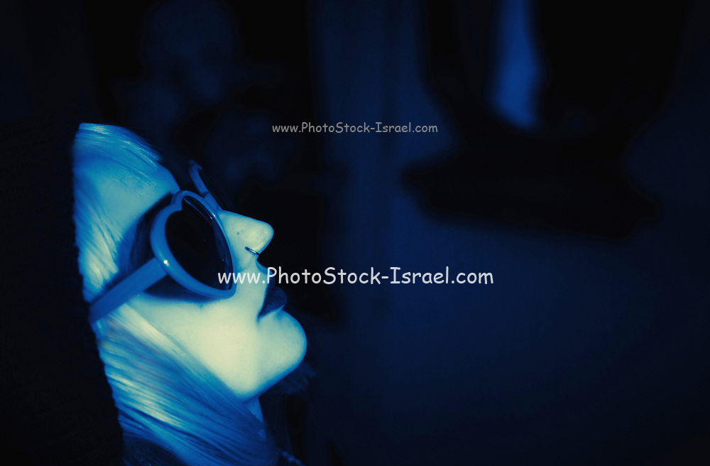 Blond model with sun glasses in blue light