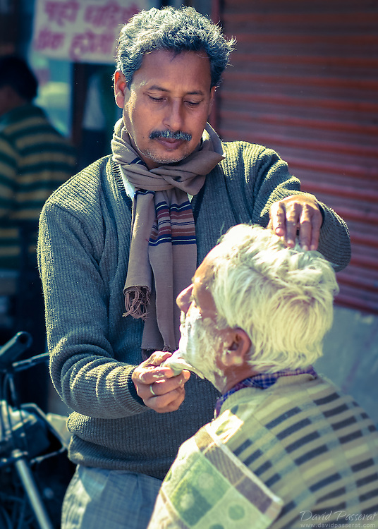 Very common in India it is to get shaved in the street and talk about daily life.