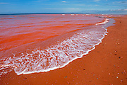 Waves along the sandy beach of red soil along the Gulf of St. Lawrence