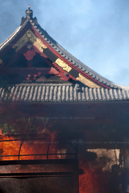 Smoke and flames billow from the incinerator in front of the Temple roof at the Ningyo Kuyo matsuri or festival of last rights for the memory of beloved, old dolls in Kiyomizu Kannon-do Temple in Ueno Park, Tokyo, Japan September 25th 2009