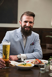 Well-dressed man holding beer glass and eating food at restaurant