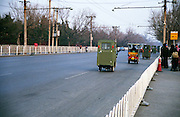 Chinese three-wheel taxis on a road in Beijing. Quick but not particularly comfortable.