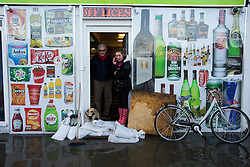 © Licensed to London News Pictures. 27/12/2015. York, UK.  Shop workers in York start sand bagging the doorway to their shop in anticipation of further flooding. Large areas of the North of England have been hit by severe flooding following unusually heavy rainfall in December. Photo credit: Ben Cawthra/LNP