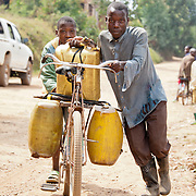 Habanabakize, assisted by friend Jean de Dieu, pushes a bicycle loaded with 60 gallons of water in jerry cans through the rural streets of Rulindo, Rwanda.