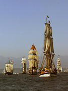 Tall Ships form up to parade in Elliott Bay.  At right center is the Lady Washington, directly behind to the left is the Hawaiian Chieftian, at far right in the distance is the tallest Tall Ship the Europa. (Greg Gilbert / The Seattle Times, 2002)