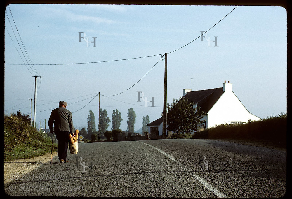 Man walks home on country road in Brittany with day's supply of French bread in straw basket. France