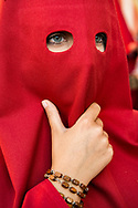 A woman belonging to a brotherhood with her scarlet red hood. Cordoba, Spain.