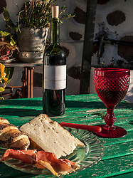 Red wine, jam and goat cheese on green wooden table