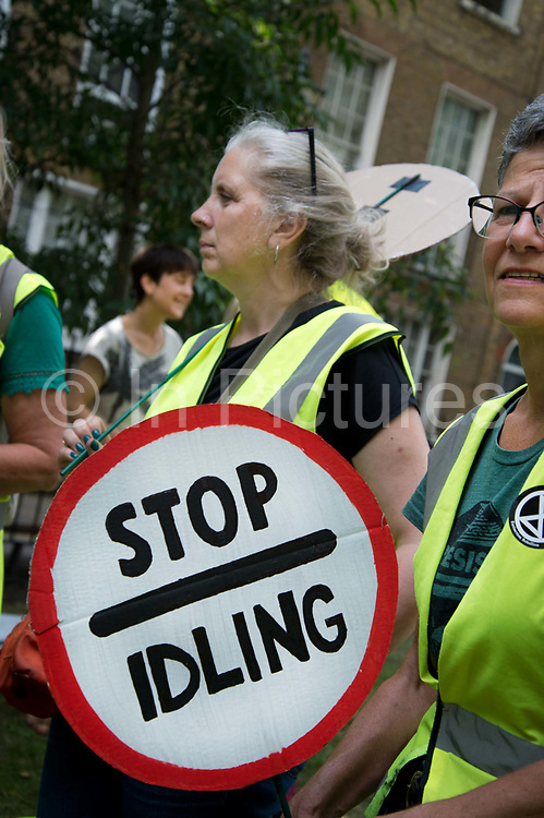 The Air that we Grieve march on July 12th 2019 in East London, United Kingdom. Organised by Extinction Rebellion to draw attention to air pollution and the climate emergency. A woman holds a placard in the shape of a traffic sign saying No idling refering to drivers who leave car engines running.