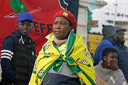 Wednesday 8th May 2019.<br /> Monwabisi Park, Harare,<br /> Khayelitsha, Cape Town, <br /> Western Cape, <br /> South Africa.<br /> <br /> SOUTH AFRICAN GENERAL ELECTIONS 2019!<br /> <br /> SOUTH AFRICAN PROVINCIAL AND NATIONAL ELECTIONS 2019! <br /> <br /> An ANC supporter wears ANC colours as she walks past some EFF supporters outside the voting station at Monwabisi Park, Harare in Khayelitsha near Cape Town, Western Cape, South Africa.<br /> <br /> Registered South African Voters head to the various IEC (Independent Electoral Commission) Voting Stations where they are registered to vote as they cast their votes and take part in voting and other activities on Voting Day 8th May 2019 during the South African General Elections 2019. Voters from across the nation stood in queue's along with many others to vote in the Provincial and National Elections being held in South Africa on Wednesday 8th May 2019.   <br />  <br /> Copyright © Mark Wessels. All Rights Reserved. No Usage Without Permission.<br /> <br /> PICTURE: MARK WESSELS. 08/05/2019.<br /> +27 (0)61 547 2729.<br /> mark@sevenbang.com<br /> studioseven@mweb.co.za<br /> www.markwesselsphoto.com