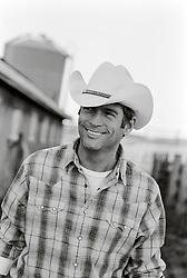 good looking All American Cowboy in a barn wearing a plaid shirt