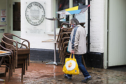 Chesham, UK. 18th June, 2021. A man's umbrella blows inside out on a wet and windy day coinciding with the Liberal Democrats' victory in the Chesham and Amersham by-election. The Liberal Democrat candidate, Sarah Green, won by 8,028 votes from the Conservatives, overturning a 16,000 majority in a seat which had always voted Conservative.