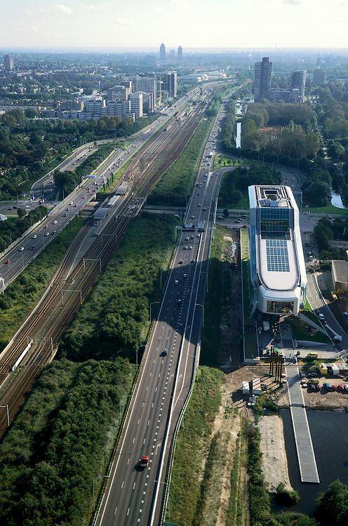 Nederland, Amsterdam, Zuidas, ringweg A10, 25-09-2002; Zuid as met  hoofdkantoor van de ING (bijgenaamd de kruimeldief) met de langgerekte vlonder die het bankgebouw met het nabij gelegen Nieuwe Meer verbindt; links - tussen beide rijbanen van de autosnelweg - het station Amstelveenseweg van de ringlijn; boven de ING: kantoortorens hoofdkantoor ABN AMRO, links hiervan WTC (World Trade Centre) met meer naar voren de Arrondissementsrechtbank aan de Parnassussweg, achter het WTC de tentoonstellingshallen van de RAI; aan de horizon: links Okurahotel, midden torens bij het Amstelstation (Breitner-, Rembrandt- en Monriaantoren met hoofdkantoor Philips); bouwen, stadsontwikkeling, bank, verzekeringen, economie, handel,  stadsgezicht, openbaar vervoer, infrastructuur; zie ook andere foto's van deze lokatie;..Zuid-as - South Axis: financial district, with head office of ING Bank at the ringroad; economy, banking, money, 'city';<br /> luchtfoto (toeslag), aerial photo (additional fee)<br /> foto /photo Siebe Swart