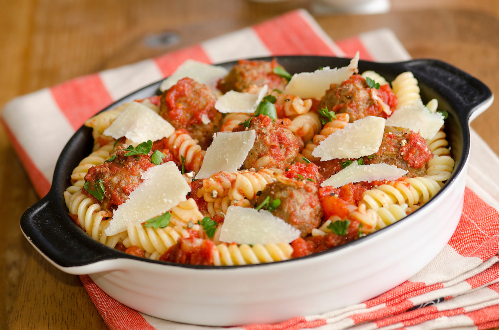 Meatballs with fusilli in tomato sauce topped with grated Parmesan
