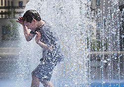© Licensed to London News Pictures. 07/07/2017. London, UK. A young visitor enjoys a splash in the fountain at the Southbank Centre as parts of the United Kingdom enjoy high temperatures and blue sky. Photo credit: Peter Macdiarmid/LNP