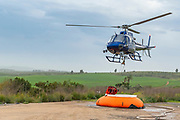 A police helicopter is used during a fire drill to airlift water to the fire zone. The water container is refilled from an inflatable pumpkin tank