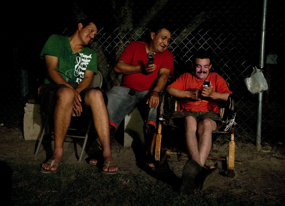 Muaro Medina, Enrigue Cordova, and Maximiliano Rubio,  watch Mexican videos on their cellphones as they hang-out in the front yard of their community house.