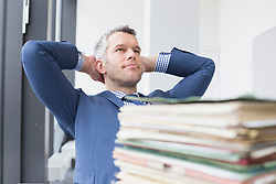 Businessman relaxing in office, Leipzig, Saxony, Germany