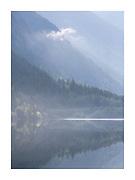 morning mist on lake surface as sun starts to shine through