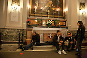 Weary pilgrims and residents of Trecastagni rest inside the church of Sant' Alfio during the Saint's feast day (festival of Sant' Alfio) which goes on late into the night.