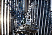 Cranes involved in construction at a major site in the City of London climb high into the sky as Tower 42 (once the Nat West Tower) looms behind as a reminder of the financial power of the City.