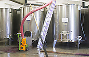 Domaine Haut-Lirou in St Jean de Cuculles. Pic St Loup. Languedoc. Stainless steel fermentation and storage tanks. Floating top vats. Pumping wine. Emptying a vat to fill the press with grapes. France. Europe.