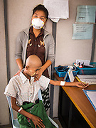 03 MARCH 2104 - MAE KASA, TAK, THAILAND: A medic comforts a woman with TB at the Sanatorium Center for Border Communities in Mae Kasa, about 30 minutes north of Mae Sot, Thailand. The Sanatorium provides treatment and housing for people with tuberculosis in an isolated setting for about 68 patients, all Burmese. The clinic is operated by the Shoklo Malaria Research Unit and works with several other NGOs that assist Burmese people in Thailand. Reforms in Myanmar have alllowed NGOs to operate in Myanmar, as a result many NGOs are shifting resources to operations in Myanmar, leaving Burmese migrants and refugees in Thailand vulnerable. Funding cuts could jeopardize programs at the clinic. TB is a serious health challenge in Burma, which has one of the highest rates of TB in the world. The TB rate in Thailand is ¼ to ⅕ the rate in Burma.        PHOTO BY JACK KURTZ