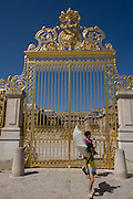 Tourists pose for photos beneath the golden gates of the Palace of Versaille, near Paris. A total of 100,000 gold leaves were crafted into the shapes of fleur de lys, crowns, masks of Apollo, cornucopias and the crossed capital Ls representing the Sun King. Private donors contributed £4 million to rebuild the 15-ton work, and a plethora of historians and top craftsmen - sculptors, gilders, wrought iron craftsmen and ornament makers - were drafted in to ensure an exact replica of the original built by Jules Hardouin-Mansart in the 1680s.