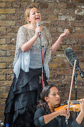 The actual perfomance takes place under a railway arch due to the heavy rain. Charlotte Church, Welsh singer, performs outside Shell HQ as part of month long protest against Arctic drilling from Greenpeace. The protest involves the string section of a classical orchestra performing a daily Requiem for the Arctic Ocean. Shell Centre, Southbank, London, UK 26 Aug 2015