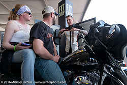 """Amber and Aaron Healy of Sioux Falls, SD try out different seats in the """"Fit Shop"""" area of the Harley-Davidson display in Daytona International Speedway during the Daytona Bike Week 75th Anniversary event. FL, USA. Saturday March 5, 2016.  Photography ©2016 Michael Lichter."""