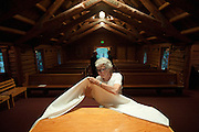 PRICE CHAMBERS / NEWS&GUIDE<br /> Shirley Craighead, sacristan for the chapel, folds the alter cloth after Mass.